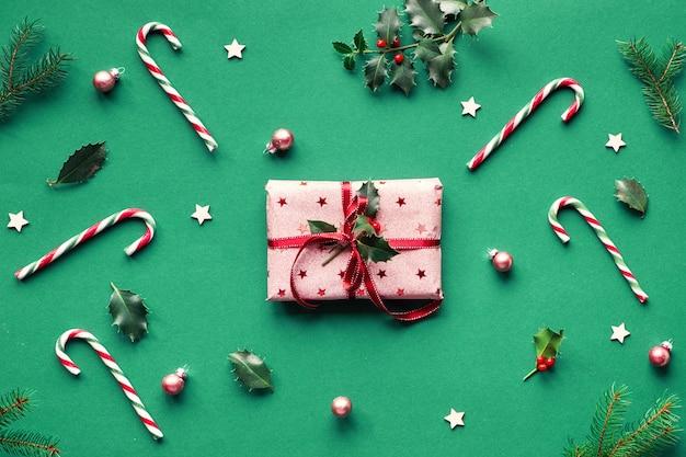 Die trendige weihnachtswohnung lag auf grünem papierhintergrund mit zuckerstangen, stechpalmen- und tannenzweigen, holzsternen und schmuckstücken. geschenkbox eingewickelt in rosa geschenkpapier mit rotem band und natürlichem stechpalmenzweig.