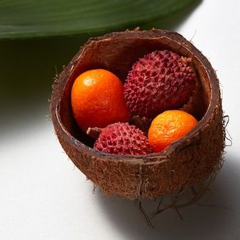 Die tropischen exotischen früchte lytchi und kumquat in der kokosnussschale mit immergrünen blättern lokalisiert auf einem weißen hintergrund. nahaufnahmefoto.