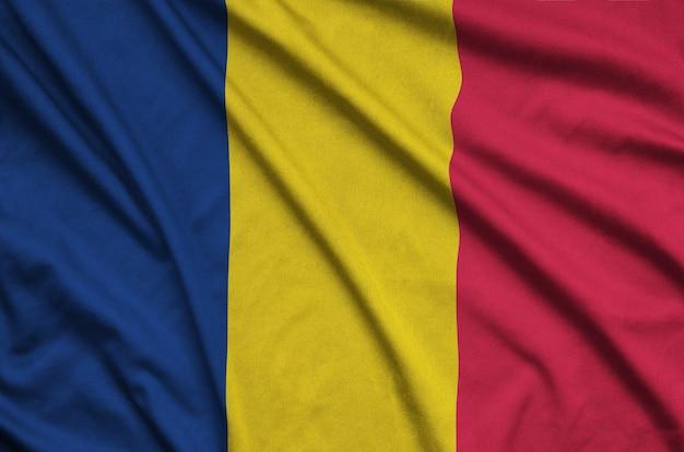 Die tschadische flagge ist auf einem sportstoff mit vielen falten abgebildet.