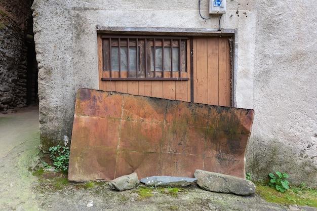 Die tür eines alten lagerhauses oder blocks, die bei schlechtem wetter mit einem rostigen blech bedeckt ist