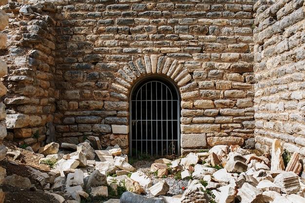 Die tür stammt aus dem metallgitter eines antiken gebäudes, einer burg aus stein mit weitläufigen blöcken.