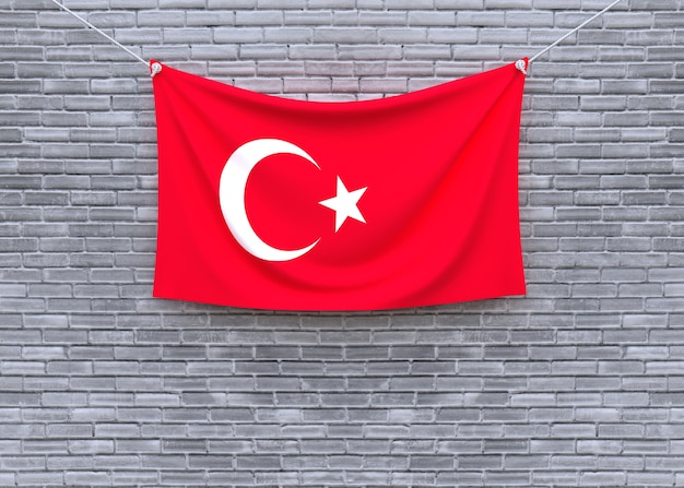 Die türkei-flagge, die an der backsteinmauer hängt