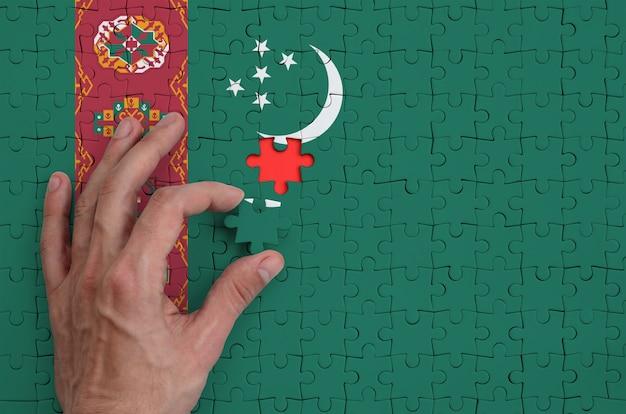 Die turkmenische flagge ist auf einem puzzle abgebildet, das mit der hand des mannes gefaltet wird