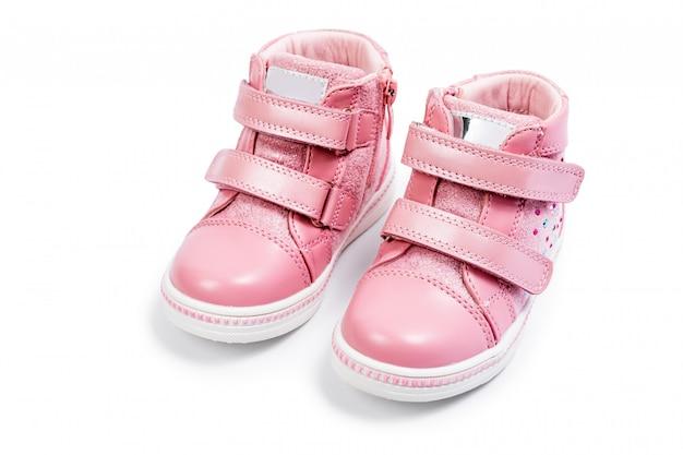 Die turnschuhe der rosafarbenen kinder getrennt auf einem weiß