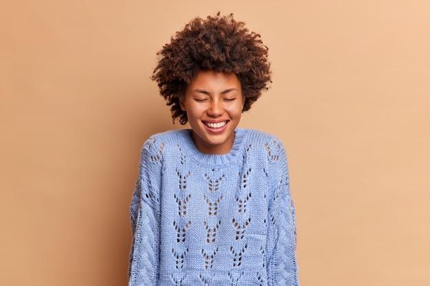 Die überglückliche hübsche frau mit dem lockigen haar lächelt breit und schließt zufrieden die augen. sie hört etwas sehr lustiges, gekleidet in einen lässigen blauen pullover, der positive emotionen ausdrückt, die auf der beigen wand isoliert sind