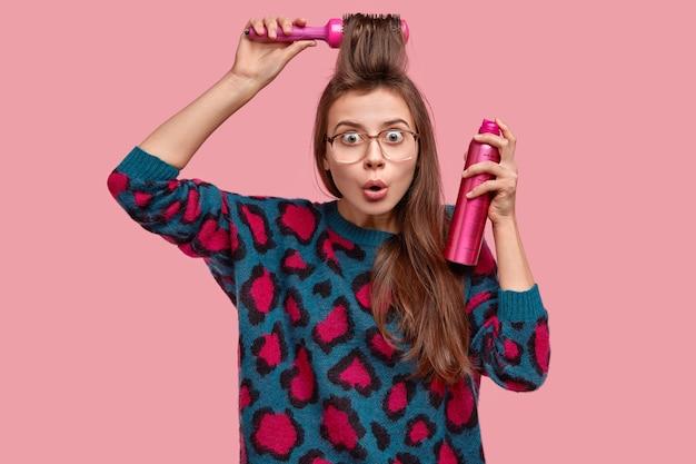 Die überraschte frau macht haare, sprüht fransen, benutzt eine haarbürste, trägt eine brille und einen pullover