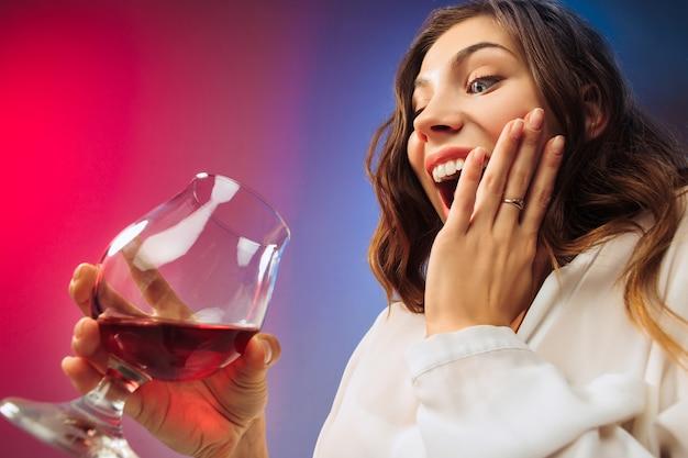 Die überraschte junge frau in partykleidung posiert mit einem glas wein. emotionales weibliches süßes gesicht. blick aus dem glas