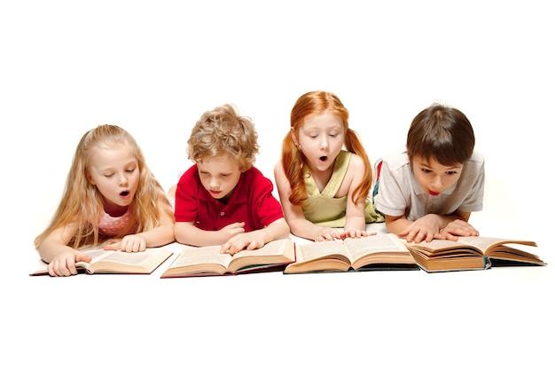 Die überraschten kinderjungen und -mädchen, die mit büchern im studio legen, lächeln, lachen, lokalisiert auf weiß. tag des buches, der bildung, der schule, des kindes, des wissens, der kindheit, der freundschaft, des studienkinderkonzepts