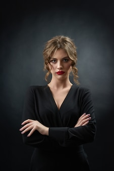 Die überzeugte frau, die roten lippenstift und stilvolles schwarzes kleid trägt, wirft vor kamera auf dunkelgrauem hintergrund auf