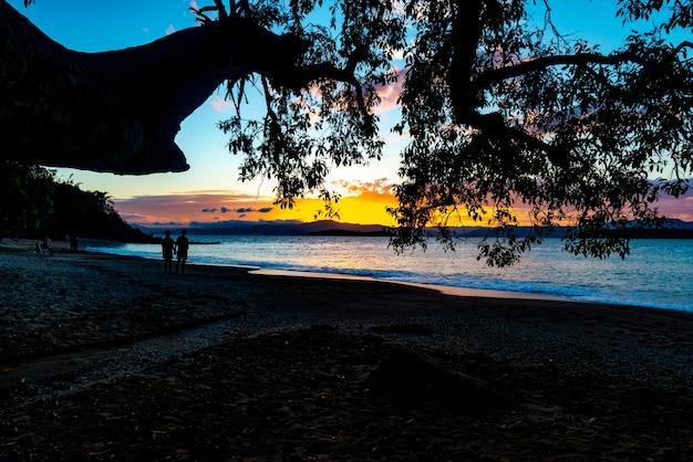 Die üppigen farben des sonnenuntergangs am strand von ponta do sambaqui in florianópolis, santa catarina, brasilien.
