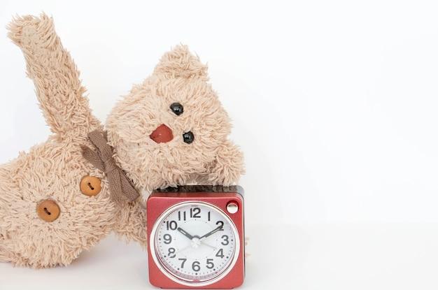 Die uhr und ein süßer teddybär zeigen eine einfache yoga-pose zum dehnen und stärken.