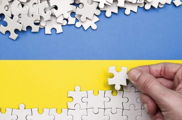 Die ukrainische flagge ist auf einem tisch abgebildet, auf dem die menschliche hand ein puzzle weißer farbe faltet