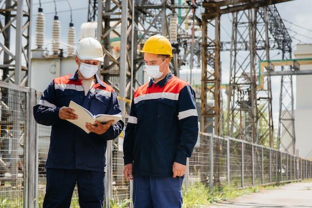 Die umspannwerke der ingenieure führen zum zeitpunkt der pandämie eine untersuchung moderner hochspannungsgeräte in der maske durch. energie. industrie.