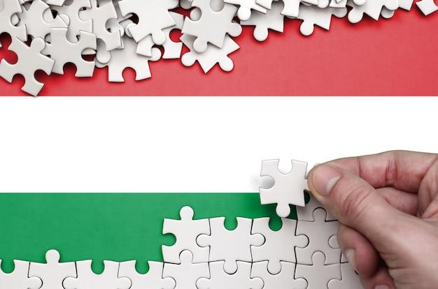 Die ungarische flagge ist auf einem tisch abgebildet, auf dem die menschliche hand ein puzzle weißer farbe faltet
