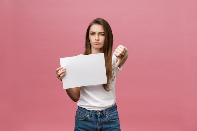 Die unglückliche frau, die daumen gibt, gestikulieren unten mit leerem papier und negativem ausdruck