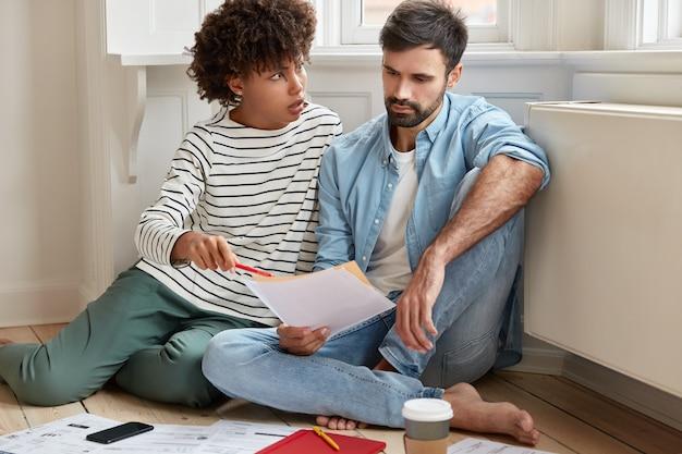 Die unzufriedene dunkelhäutige geschäftsfrau überzeugt ihren ehemann, auf einige zahlen im finanzbericht zu achten