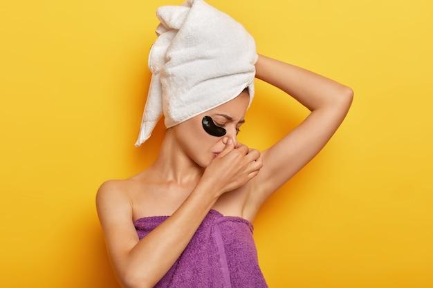 Die unzufriedene junge dame riecht nach verschwitzter achselhöhle, bedeckt die nase vor unangenehmem geruch, trägt unteraugenflecken auf, trägt ein handtuch auf dem kopf und um den nackten körper und muss isoliert über der gelben wand duschen