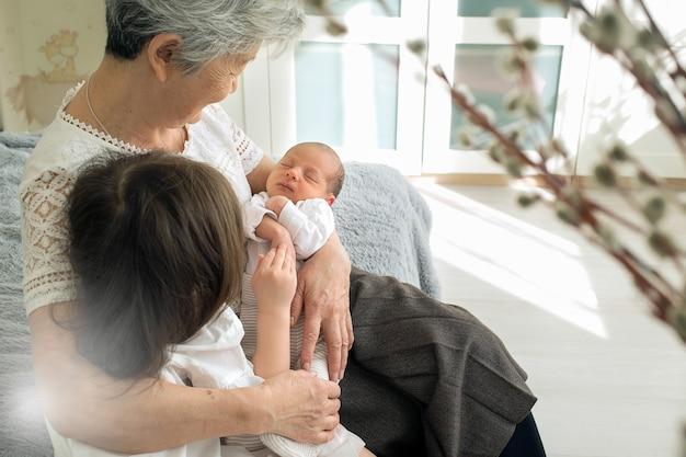 Die urgroßmutter umarmt zwei urenkelinnen.