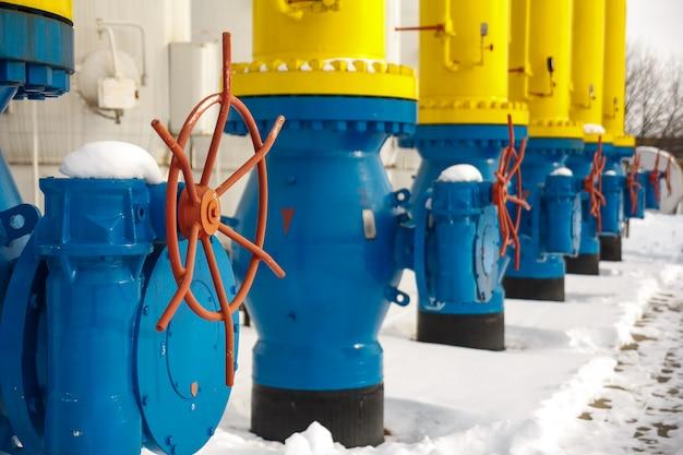Die ventile zum öffnen und schließen der gasversorgung an der gaskompressorstation im winter. blaue rohre für den gastransport an der gaskompressorstation mit roten ventilen zum ein- und ausschalten der gasversorgung.