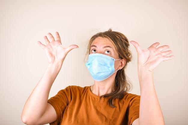 Die verängstigte frau in der medizinischen maske bedeckt ihr gesicht mit ihren händen, isoliert auf dem weißen raum