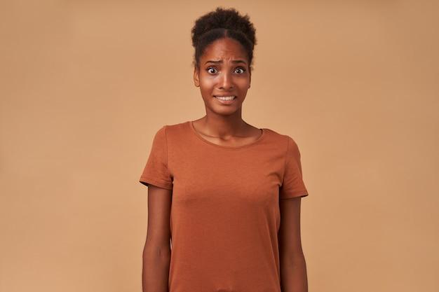 Die verängstigte junge dunkelhäutige brünette trägt ihr lockiges haar im knoten, während sie mit gesenkten händen auf beige posiert und verwirrt ihr gesicht verzieht