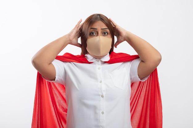 Die verängstigte superheldenfrau mittleren alters, die eine medizinische maske trug, packte den kopf isoliert auf weiß
