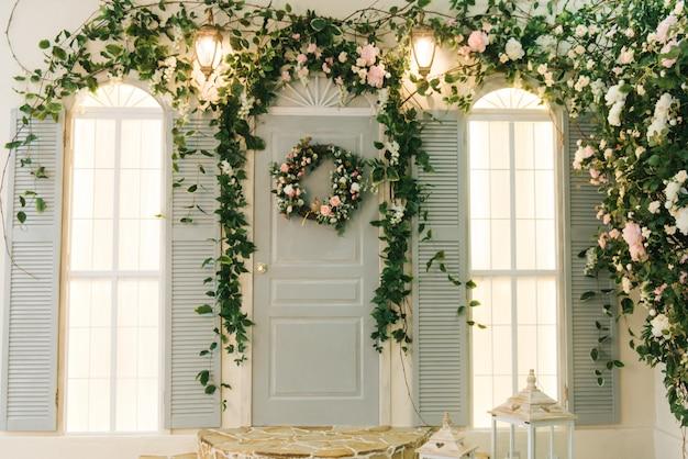 Die veranda des hauses mit fenstern ist mit schönen grünen blumen, frühlingsdekor dekoriert