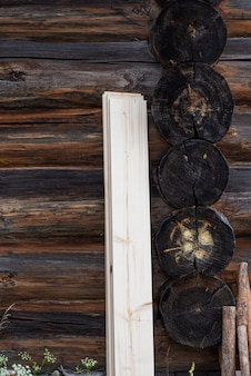 Die verdunkelte wand eines traditionellen holzhauses frisches brett steht gegen eine holzwand