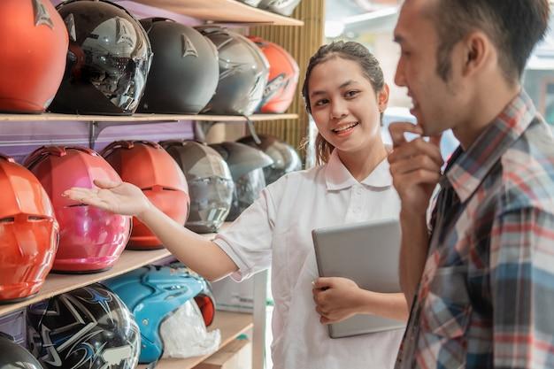 Die verkäuferin einer frau, die ein tablet in einer handbewegung hält, bietet dem mann im helmgeschäft einen helm an