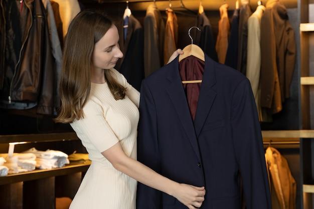 Die verkäuferin lächelt und zeigt die kleider im kostümladen und spricht in die kamera