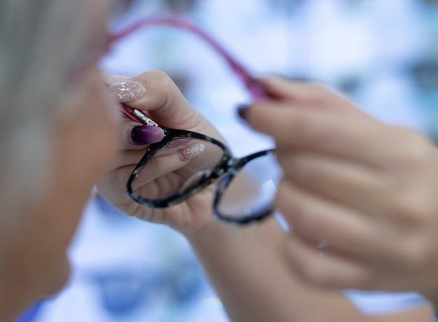 Die verkäuferin mit verzierten nägeln im französischen stil probiert die brille der kundin aus. zwei personen weiblich