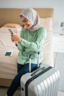 Die verschleierte frau saß auf dem bett und hielt ihr smartphone und ihren koffer