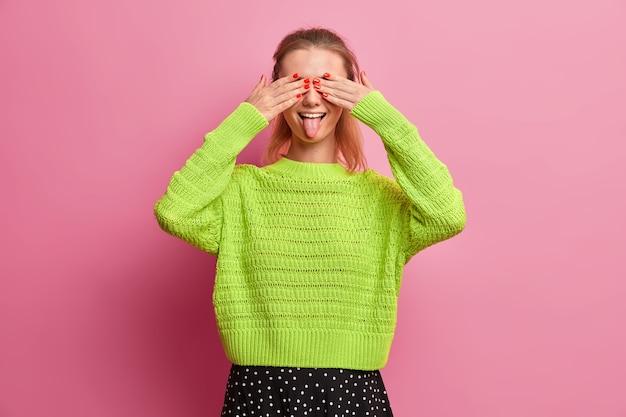 Die verspielte frau bedeckt die augen und streckt die zunge heraus, hat spaß und ist dumm, spielt mit ihrer jüngeren schwester, gekleidet in einen locker gestrickten grünen pullover