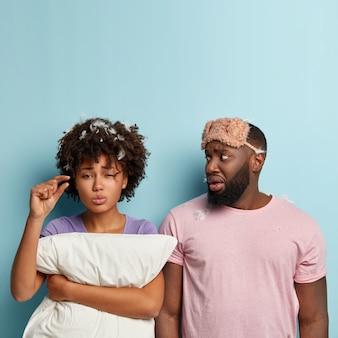 Die vertikale einstellung einer unzufriedenen frau zeigt eine kleine handbewegung, sagt, sie habe wenig geschlafen, bittet um zeit zur ruhe, der nervöse ehemann im lässigen t-shirt und die augenmaske sehen die frau an. schlafenszeitkonzept