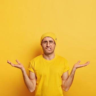 Die vertikale einstellung eines ahnungslosen, verwirrten mannes spreizt zögernd und unbewusst die handflächen, beißt sich auf die lippen, drückt unsicherheit und zweifel aus
