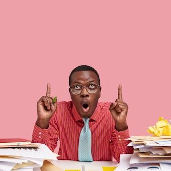 Die vertikale einstellung eines verblüfften schwarzen mannes öffnet vor erstaunen den mund, zeigt mit beiden zeigefingern nach oben und bemerkt etwas unerwartetes an der decke