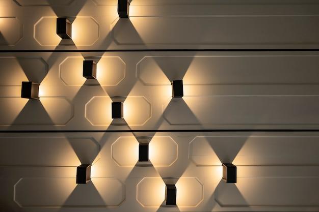 Die vertikale lampe hängt mit wolframlicht daneben an der horizontalen wand.