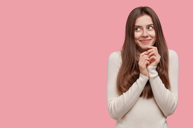 Die verträumte brünette frau lächelt sanft, hält die hände unter dem kinn zusammen und trägt freizeitkleidung
