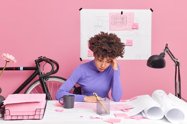 Die verwirrte architektin verbessert die grafik, korrigiert fehler, die mit der arbeit an einem architekturprojekt beschäftigt sind, und hat fristen auf dem desktop, die von papieren umgeben sind, um das problem zu lösen