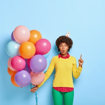 Die verwunderte frau hält bunte luftballons, während sie in einem gelben pullover posiert