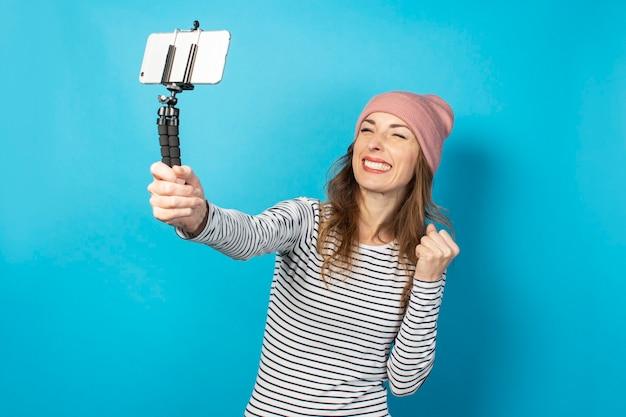 Die videobloggerin einer jungen frau fotografiert sich selbst am telefon, während sie auf einer blauen oberfläche sendet