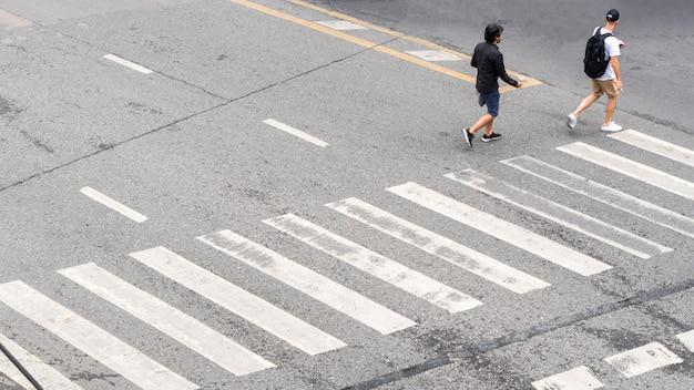 Die vielbeschäftigten stadtbewohner begeben sich auf den fußgängerüberweg auf der geschäftsverkehrsstraße