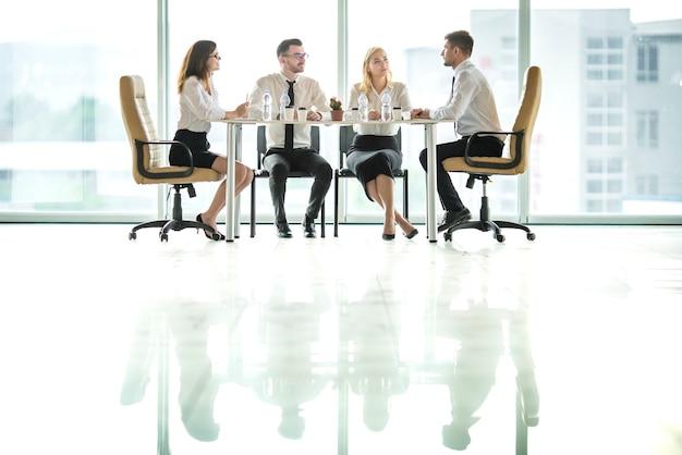 Die vier geschäftsleute sitzen am tisch und diskutieren