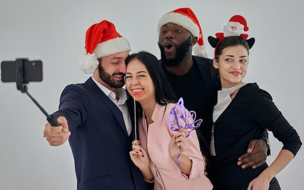 Die vier glücklichen geschäftsleute, die ein weihnachts-selfie machen