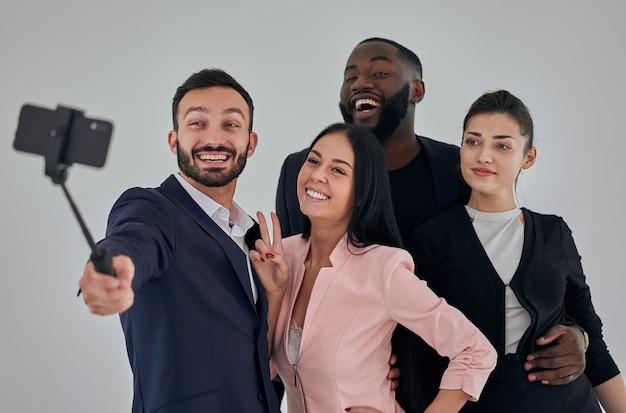 Die vier glücklichen geschäftsleute machen selfie