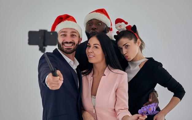 Die vier glücklichen geschäftsleute mit rotem hut machen selfie