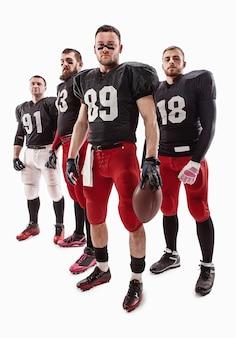 Die vier kaukasischen fitness-männer als american-football-spieler posieren in voller länge mit einem ball auf weiß