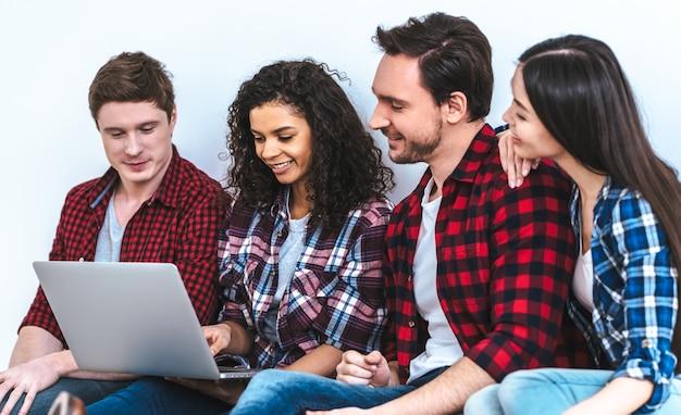 Die vier leute mit einem laptop, die auf dem weißen wandhintergrund sitzen