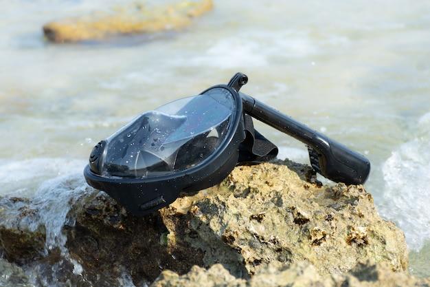 Die vollgesichts-schnorchelmaske liegt an der von den wellen umspülten küste