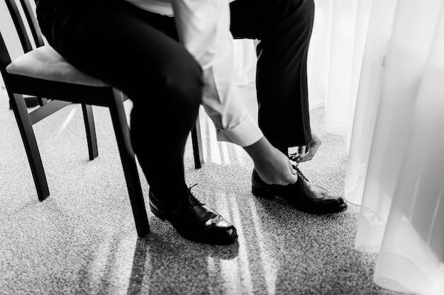 Die vorbereitungen des bräutigams für die hochzeit. gebühren des bräutigams. schwarzweiss-fotokonzept der hochzeit. nahansicht.